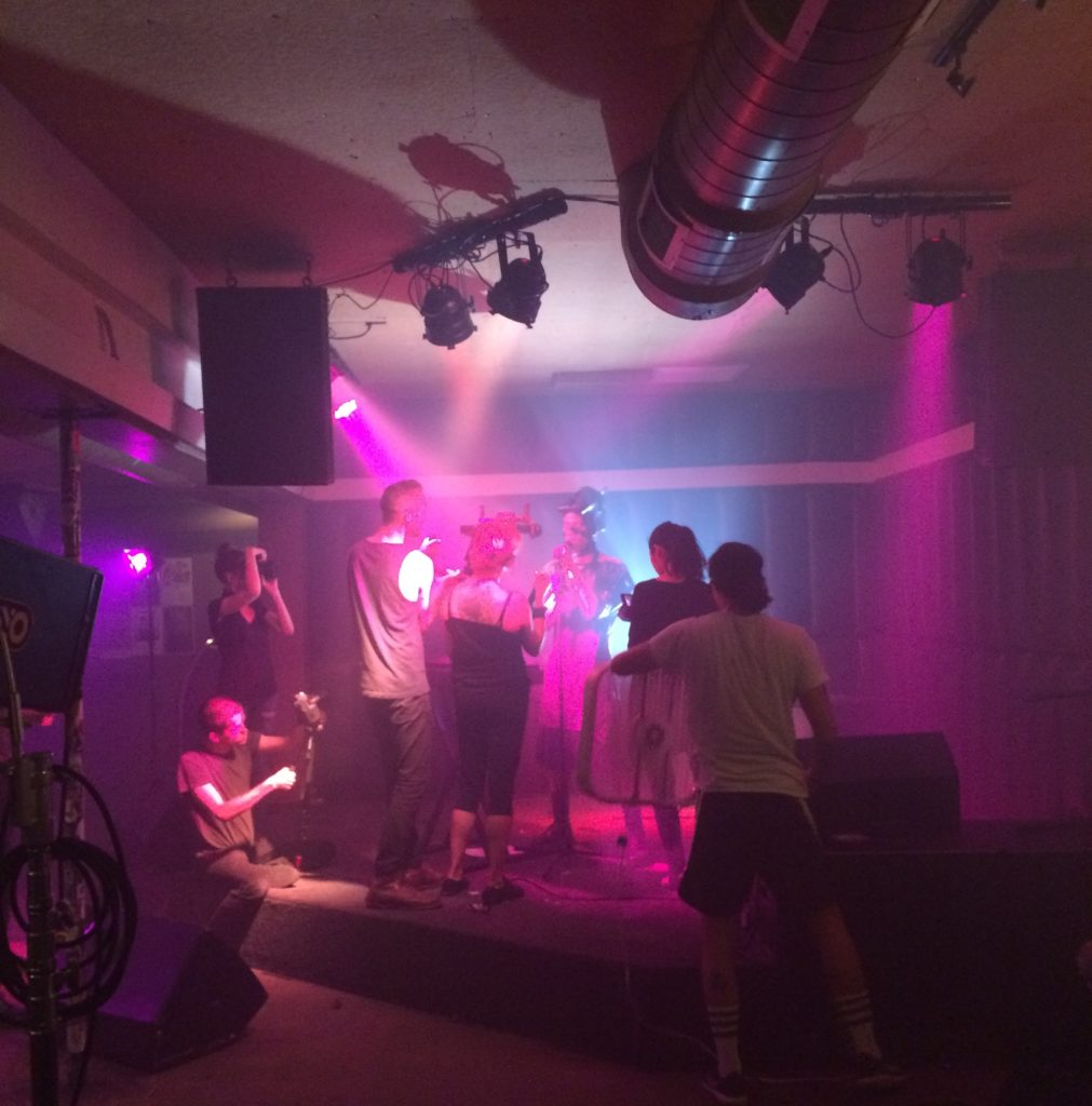 The far end of a dark space is lit up bright pink where a film crew is clustered on a small stage.